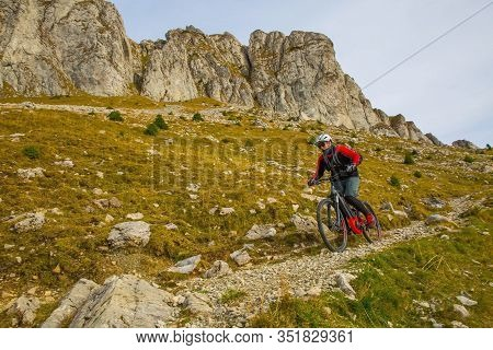 Young Boy Cycling Throuh Rocky Terrain With His Trail Bike