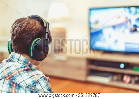 Young Kid Playing Mass Multiplayer Game Online, Back View