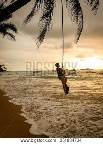 Beautiful Image Of Sexy Yougn Woman In Swimsuit Swinging On The Rope Tied To The Palm Tree Over The