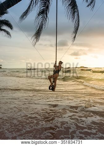 Photo Of Sexy Young Woman Swinging On The Palm Tree At Sunset On The Beach