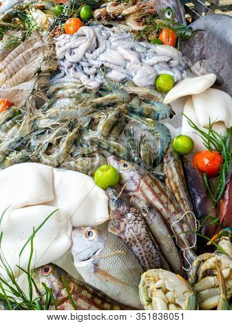 Closeup Image Of Big Assortment Of Fresh Tasty Uncooked Seafood And Vegetables On The Market