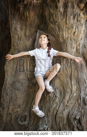 Pretty Lovely Young Girl With Pigtails Wearing White Shirt Sitting And Spreading Arms In The Stem Of