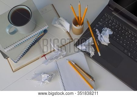 Top View On Chaos Or Mess On White Table With Black Laptop, Books, Cup Of Coffee And Yellow Pencils