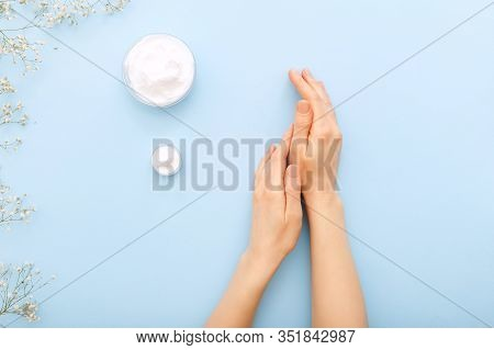 Hand Cream, Female Hands Applying Organic Natural Cream Cosmetics On A Pastel Blue Colored Backgroun