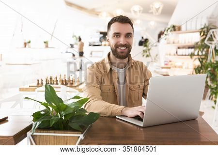 Young Handsome Smiling Man Works In His Laptop During Lunch Break At Cafe Looks Happy, Multitasking