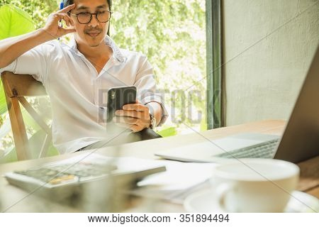 Businessman Looking At Cell Phone With Laptop And Calculator On Table