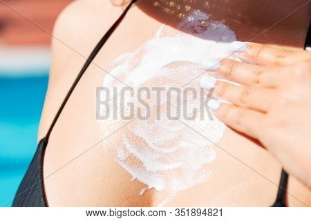 Pretty Girl Putting Sun Cream On Her Breast Near The Pool. Sun Protection Factor In Vacation, Concep