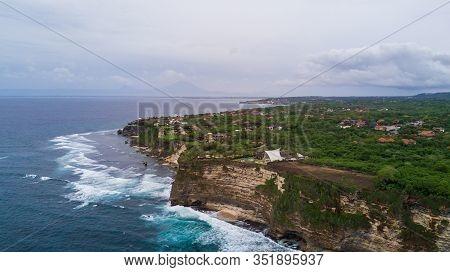 Aerial View Of Sea Rocky Coast With Surf The Waves, Bali, Indonesia, Pura Uluwatu Cliff. Waves Crush