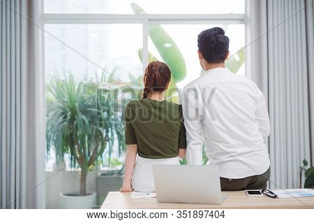 Cute Couple Looking Out The Window After Work