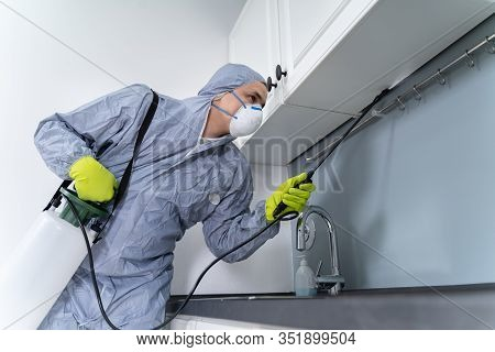Side View Of Exterminator In Workwear Spraying Pesticide In Kitchen. Pest Control