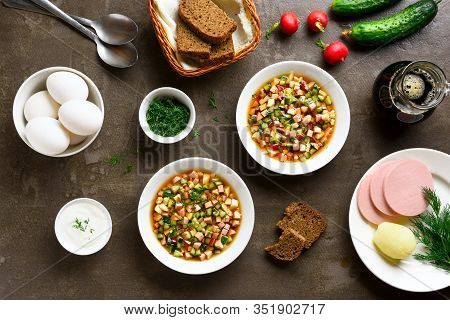 Traditional Cold Russian Okroshka Soup And Ingredients Over Brown Stone Background. Tasty Summer Dis