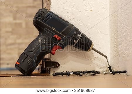 A Black Home Electric Screwdriver Leaned Against The Wall. There Are Screws Next To The Screwdriver.