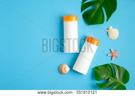 Suntan Or Sunblock Lotions Bottles On Blue Background With Tropical Leaves And Seashells. Top View W