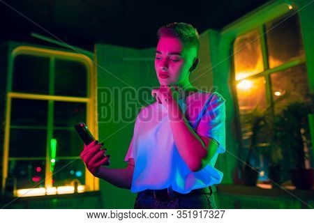 Thoughtful. Cinematic Portrait Of Stylish Woman In Neon Lighted Interior. Toned Like Cinema Effects,