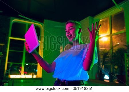 Astonished. Cinematic Portrait Of Stylish Woman In Neon Lighted Interior. Toned Like Cinema Effects,