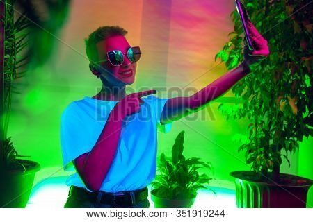 Pointing. Cinematic Portrait Of Stylish Woman In Neon Lighted Interior. Toned Like Cinema Effects, B