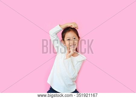 Funny Little Asian Kid Girl With Expression Monkey Face And Hands Isolated On Pink Background. Amusi