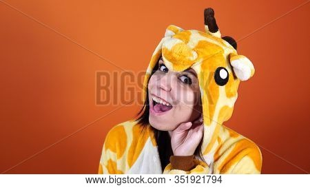 A Funny Woman In A Big Pajamas Of Giraffe Holds A Hand At Her Ear And Tries To Overhear Conversation