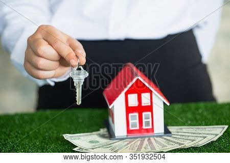 Red Roof House On Banknote, Trading House Concept. Businessman Hand Or Key Catch Agent.red House Rea