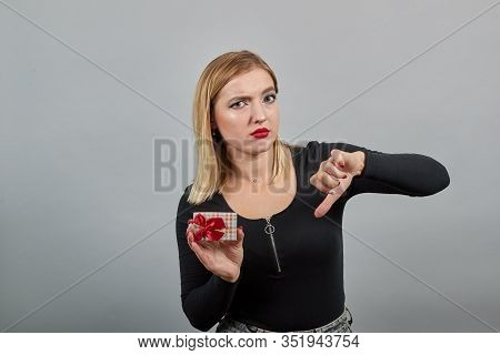 Young Blonde Girl In Black Jacket On Grey Background Upset Woman Holds Gift Packed Box In Hand, Thum