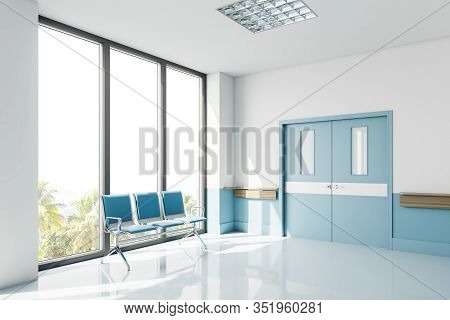 Empty White And Blue Hospital Corridor Corner With Ward Doors And Row Of Chairs For Patients Near Bi