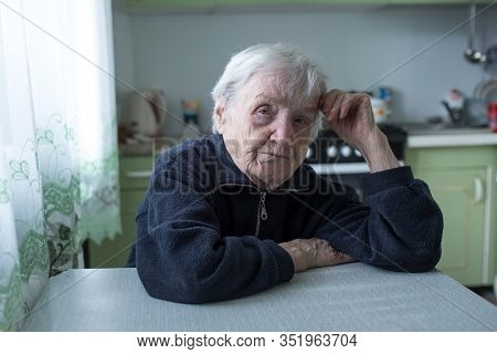 Portrait of an elderly old woman sitting at the table in kitchen.
