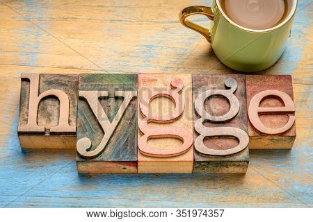 hygge word in vintage letterpress wood type blocks against grunge woodwith a cup of coffee, Danish comfortable and cozy lifestyle concept