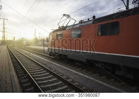 Electric Locomotive On Railroad Tracks In Singern Train Station, Germany, At Sunset. Eco-friendly Pu