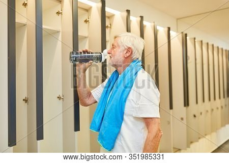 Senior man drinking after workout from a water bottle in the locker room in the gym