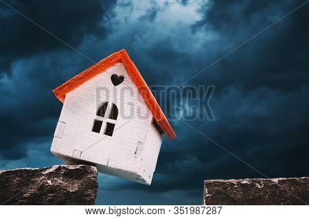 A Toy House On A Cliff Of Rock Amid A Grim Sky. Concept On Outstanding Debt For Mortgage Lending