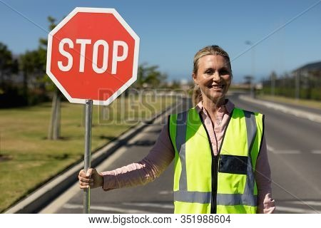 Portrait of a blonde Caucasian woman wearing a high visibility vest and holding a stop sign smiling to camera, standing in the road on a pedestrian crossing to help children cross the street safely