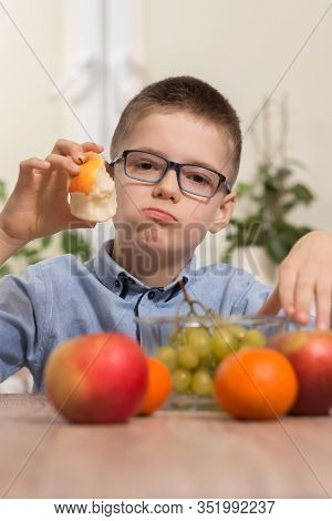 The Boy In A Blue Shirt And Glasses Sits At The Table And Holds In His Hand An Apple Which He Eats W