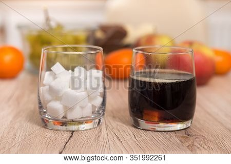 A Glass Filled With Sugar Cubes And A Glass With Cola Are Standing On The Table. In The Background,