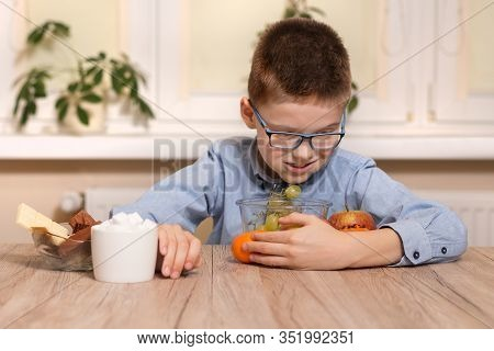 A Smiling School-age Boy Sits At A Table And Brings Fruits To Him. With The Other Hand, He Moves The