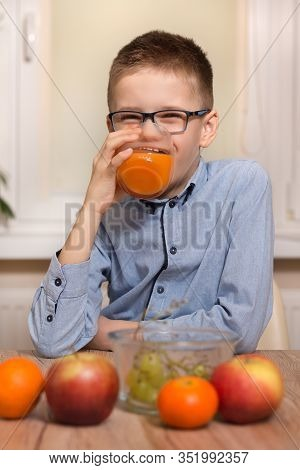 Smiling Boy Sits At The Table And Drinks Juice From A Glass. Tangerine, Apples And Grapes Lie On The