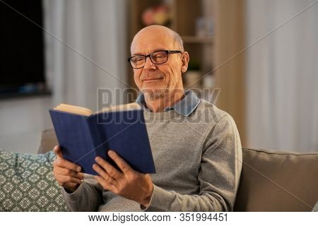 old age, leisure and people concept - happy bald senior man sitting on sofa and reading book at home in evening