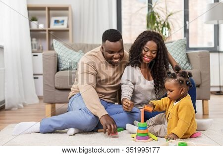 family, parenthood and people concept - happy african american mother, father and baby daughter playing with toy blocks at home
