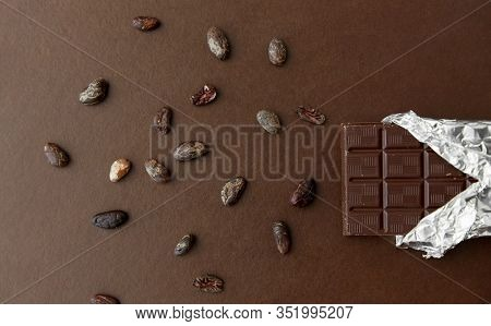 sweets, confectionery and food concept - dark chocolate bar in foil wrapper and cocoa beans on brown background