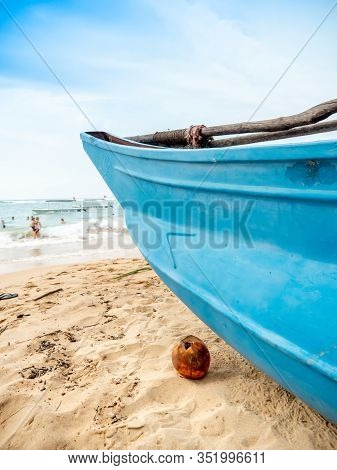 Closeup Photo Of Yellow Coconut Lying On The Ocean Baech Next To Old Wooden Fishing Boat