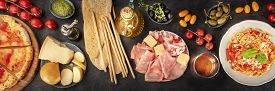 Italian Food Panorama. Pizza, Pasta, Cheese, Ham, Capers, Wine, Tomatoes, Shot From The Top On A Bla