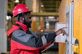 Horizontal medium side view portrait of professional Black male factory engineer setting up equipment