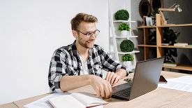 Panoramic View Of Happy Young Adult Worker Sitting In Workplace Against White Copy Space Wall On Bac