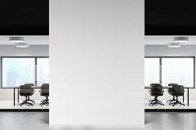Interior Of Modern Office Hall With White And Black Walls, Concrete Floor And Glass Wall Meeting Roo