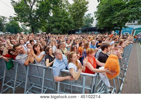 MOSCOW - JUN 23: People applaud at concert of Chaif rock-band at outdoor performance stage during VII traditional festival of live sound Music of Summer in Hermitage Garden, Jun 23 2012, Moscow Russia