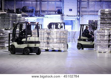 MOSCOW - MAY 31: Men work on loader machines in Ochakovo factory, on May 31, 2012 in Moscow, Russia. Moscow factory of Ochakovo company produces 750 million liters of beer annually.