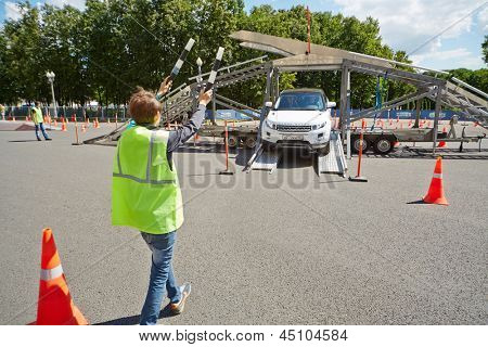 MOSCOW - JUN 30: Boy in uniform jacket with two striped traffic batons directs car driving down from auto platform at Speedfest in Luzhniki, June 22, 2012, Moscow, Russia.