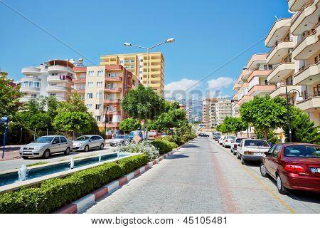 MAHMUTLAR - JUL 10: Daytime traffic at Mehmet Cakir Street, July 10, 2012, Mahmutlar, Alanya, Turkey. Mahmutlar is famous for ruins of ancient cities Siedra, Naula, Laertes.