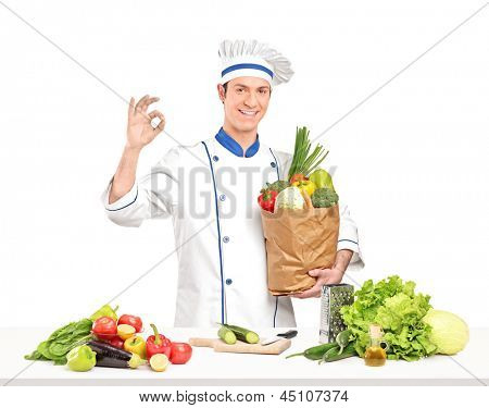 Male chef holding a paper bag full of healthy vegetable ingridients next a table, isolated on white background