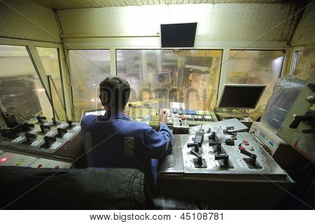 Rolling mill control cabin inside with worker.