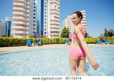 Young smling woman in pink sportswear gets out of pool half- turning back